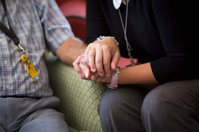Patient and carer holding hands