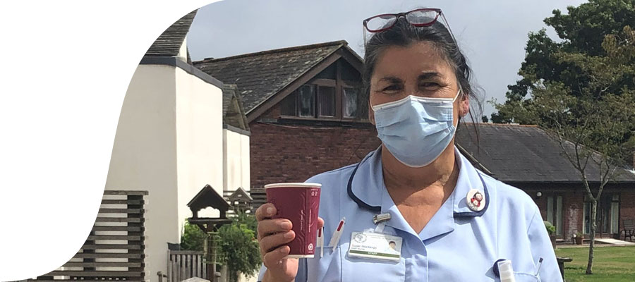 Nurse in facemask holding cup of coffee