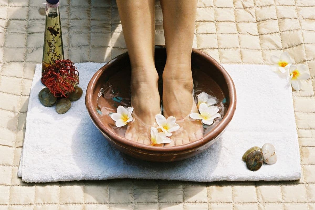 A pair of feet in a footbath with flowers