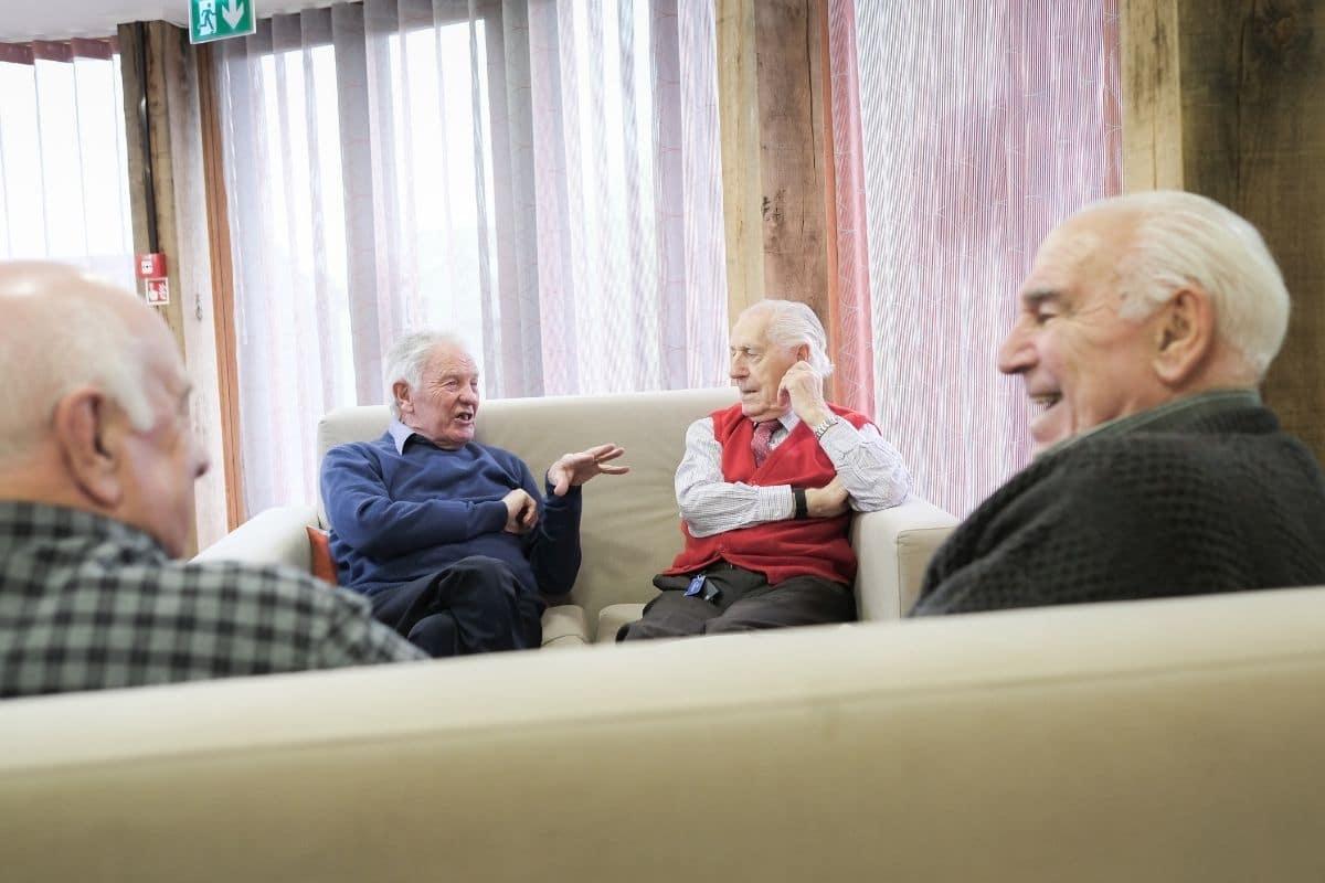 Men sat on sofas having conversations